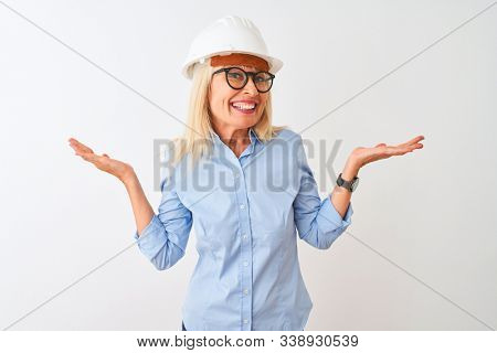 Middle age architect woman wearing glasses and helmet over isolated white background clueless and confused expression with arms and hands raised. Doubt concept. stock photo