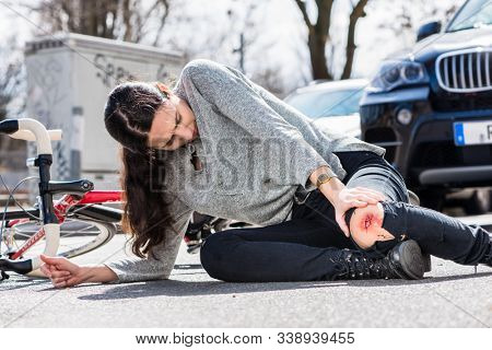 Young woman fallen down on the ground with a bleeding scrape on the knee after severe injury in bicycle accident on the street stock photo