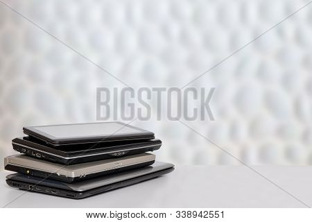 Stack of laptop computers. A pile of computers on a bright table against abstract blurred white communication and technolgy texture background. Template with space. stock photo