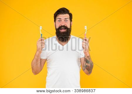 Mouth matters. Bearded man happy smile with toothbrushes. Happy hipster hold brushes yellow background. Dental hygiene. Dental clinic. Gentle dental care. Dental health. stock photo