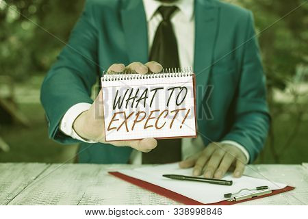 Conceptual hand writing showing What To Expect. Business photo text asking about regard something as likely to happen occur Man holds empty paper with copy space in front of him. stock photo