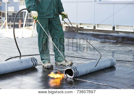 Roofer installing Roofing felt with heating and melting of bitumen roll by torch on flame during roof repair stock photo