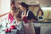 Mother with her 5 years of age children cooking occasion pie in the kitchen to Mothers day, easygoin