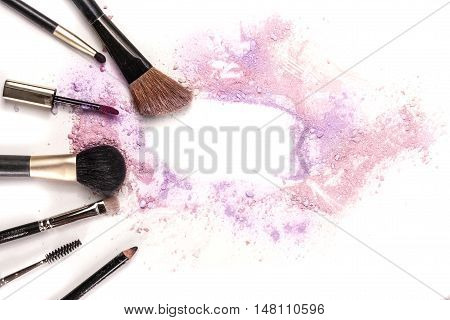 Makeup brushes, lip gloss and pencil on white background, with traces of powder and blush forming a frame. A horizontal template for a makeup artist's business card or flyer design, with copyspace stock photo