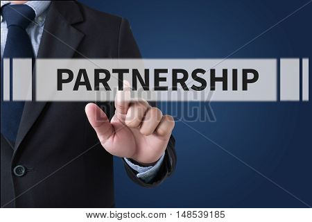 PARTNERSHIP Businessman hands touching on virtual screen and blurred city background stock photo