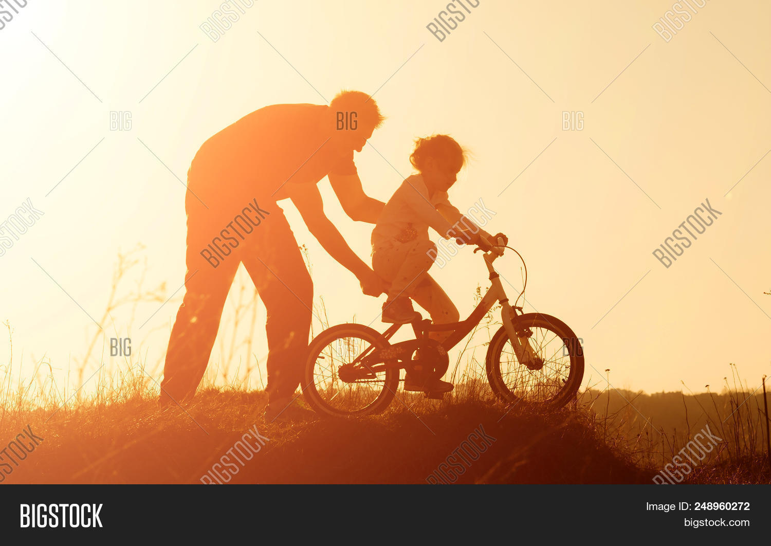 adult,bicycle,bike,care,child,childcare,childhood,dad,daddy,daughter,emotion,enjoyment,evening,family,father,field,fun,girl,happiness,happy,help,joy,kid,learning,leisure,life,lifestyle,little,loving,man,meadow,nature,orange,outdoors,parent,parenthood,scene,security,shadow,silhouette,sky,sun,sunlight,sunset,support,teaching,toddler,together,togetherness,vacation