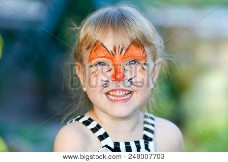 Portrait of funny girl with face painting on blurred background stock photo