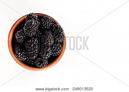 bramble in a bowl on a white background. Isolate. Blackberries in a wooden bowl with copy space for text. Ripe and tasty black berry isolated on white. Blackberries on a white background. stock photo