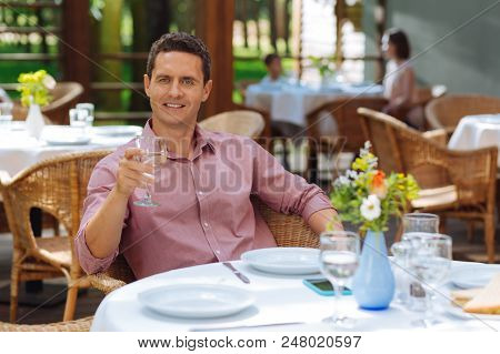 Graceful man. Graceful handsome mature man sitting at the table on summer terrace while having lunch stock photo