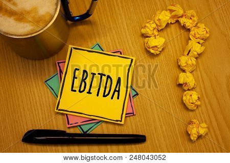 Writing note showing  Ebitda. Business photo showcasing Earnings Before Interest Taxes Depreciation Amortization Abbreviation Message wood table coffee cup question mark crumpled papers stock photo