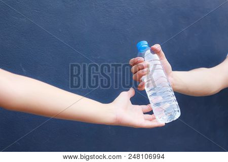 man hand clean plastic bottle full of fresh  drinking water to woman on isolated background stock photo