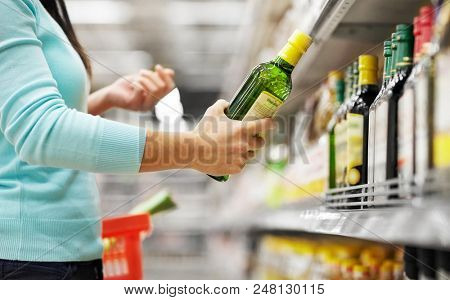 sale, shopping, food, consumerism and people concept - woman buying olive oil at grocery store or supermarket stock photo