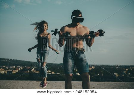 Athletes on fresh air. Athletes training together. Athlete man wear vr glasses with dumbbells while woman skipping with rope. Strong athletes outdoor. Strength on your side. stock photo