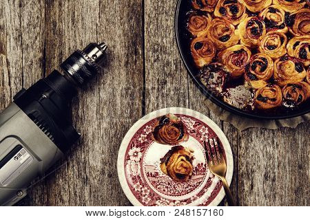 Lunch on work place. Homemade mini cherry rolls in a baking form and two rolls on a plate and electric drill on vintage wooden background.  Dissonant disharmonious composition. Lunch break. Toned stock photo