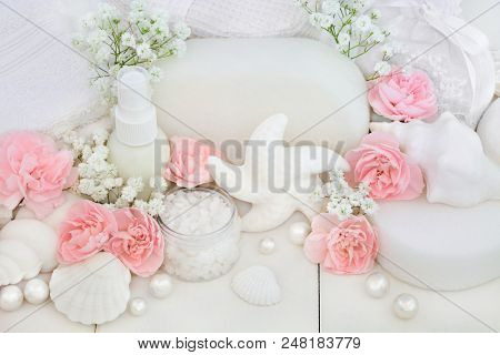 Bridal spa and beauty treatment and cleansing products with carnation flowers, ex foliating salt, seashell soaps, body lotion, sponges, wash cloths with decorative shells and pearls on white wood. stock photo