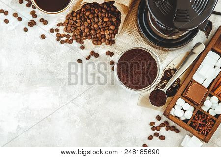 Variety things for prepare coffee. Roasted beans, ground coffee, scoop, electric coffee machine and assortment of sweets and spices to eat with stock photo