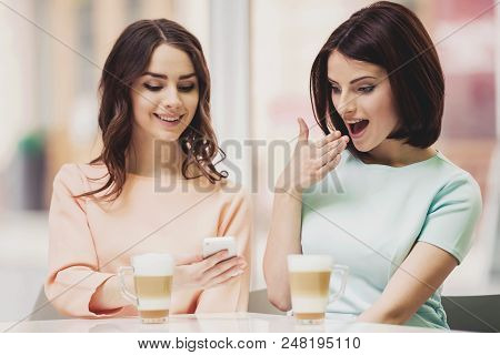Two Young Attractive Smiling Brunette Women Sitting at Table in Cafeteria with Coffe in Glass Cups and Smartphone. Smiling Cheerful Cute Girls Having Breakfast in Cafeteria Interior with Latte. stock photo