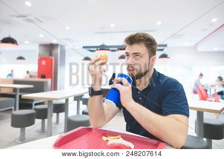 Man is sitting at the table with a fast-food tray eating a burger and drinking a cool drink from the glass. Fast food for lunch. Student eats malicious tasty food. stock photo