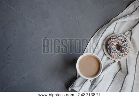 top view on Cup of coffee, a donut and a dish towel on the dark grey background stock photo