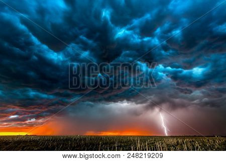 A nighttime, tornadic mezocyclone lightning storm shoots bolt of electricity to the ground and ligh