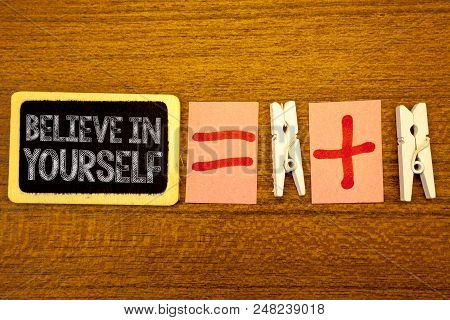 Handwriting text Believe In Yourself. Concept meaning Determination Positivity Courage Trust Faith Belief White paper clip laid woody desk black slate some texts equal and plus mark stock photo