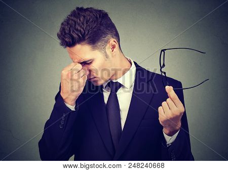 Young business man with glasses suffering from eyestrain stock photo