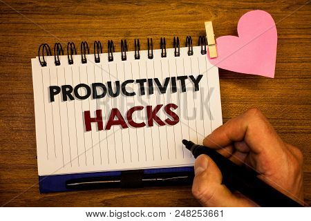 Conceptual hand writing showing Productivity Hacks. Business photo text Hacking Solution Method Tips Efficiency Productivity Human hand retain black pen notepad with words on paper pink heart stock photo