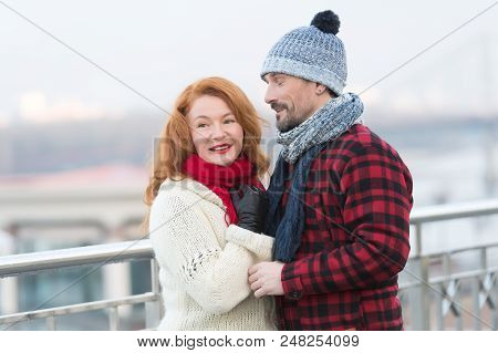 Men loves rude women with closed eyes. Guy in rad jacket and scurf happy to women in red scurf. Aged couple meet in city. City life of lovely people. stock photo