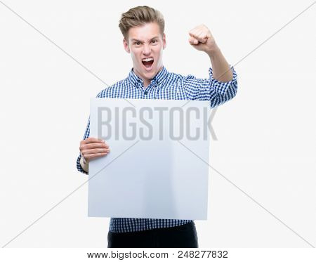 Young handsome blond man holding a banner annoyed and frustrated shouting with anger, crazy and yelling with raised hand, anger concept stock photo