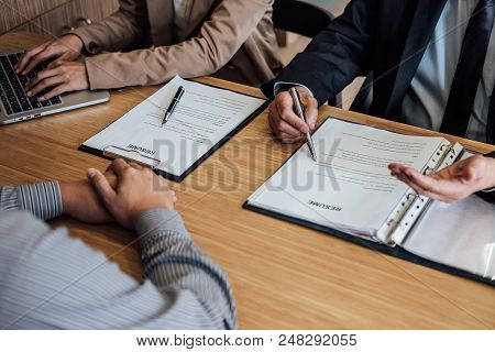 Two senior manager reading a resume during a job interview, Employer interviewing to ask young male job seeker for recruitment talking in office. stock photo