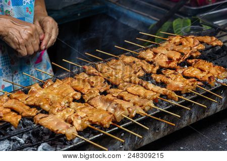 moo ping, grilled pork  skewer sticks on the bbq grill outdoor, Thai street food stock photo