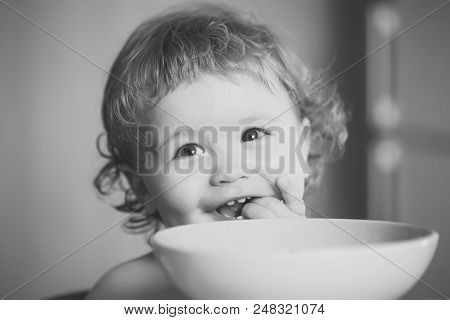 child eats porridge. Portrait of sweet little laughing baby boy with blonde curly hair and round cheecks eating from green plate holding spoon and lick fingers closeup, horizontal picture stock photo