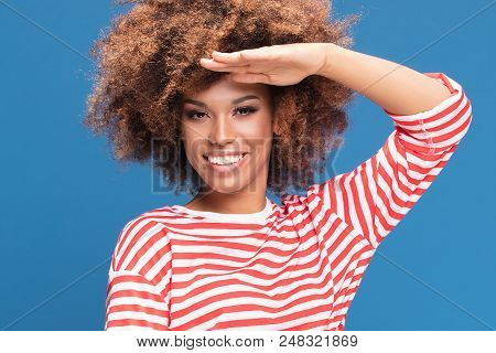 Smiling african american woman posing on blue background, wearing shirt in white and red stripes, holding inflatable circle, sailor style. stock photo