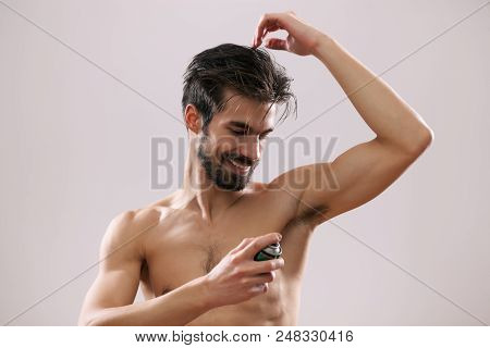 Young man is applying antiperspirant to his armpit. stock photo