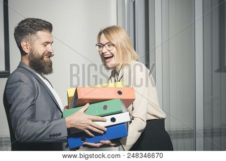 Businesswoman and businessman with folders. Man help woman to carry binders in office. Bearded man and sexy girl with documents. Office romance and flirt concept. Business cooperation and teamwork. stock photo