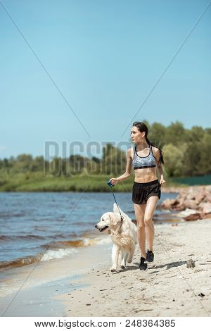 attractive young asian sportswoman running with golden retriever near sea stock photo