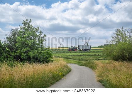 Rustic summer scenery with a country road leading towards agricultural fields and machinery collecting green fodder, near Schwabisch Hall, Germany. stock photo