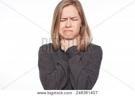 Photo of beautiful stressed irritated female makes suicide gesture, smothers herself, keeps hands on neck, looks frustrated, wears casual street style jacket, isolated over white wall. Body language. stock photo