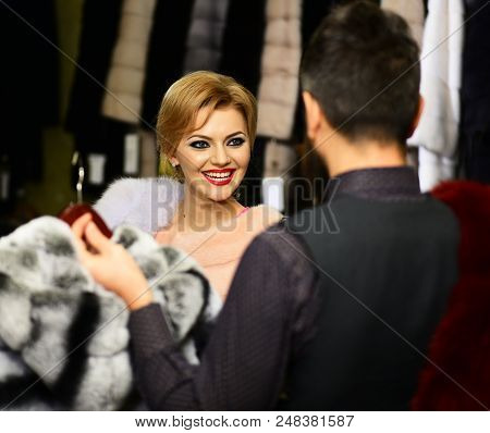 Finance and shopping concept. Man and girl with happy faces hold furry coats on clothes rack background. Shop assistant with beard and woman select furry coat. Woman chooses expensive sable overcoat stock photo