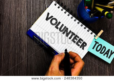 Text sign showing Volunteer. Conceptual photo Volunteering individual for greater social cause serving others Reminder appointment daily work pens penholder clip paperclip papers stock photo