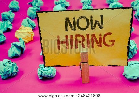 Conceptual hand writing showing Now Hiring. Business photo showcasing Workforce Wanted Employees Recruitment Today Job OpportunityClothespin hold holding Yellow paper ideas crumpled papers stock photo