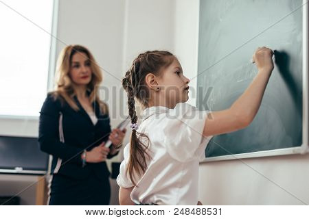 Schoolgirl first-grader writing on chalkboard. School lesson Teacher and pupil stock photo