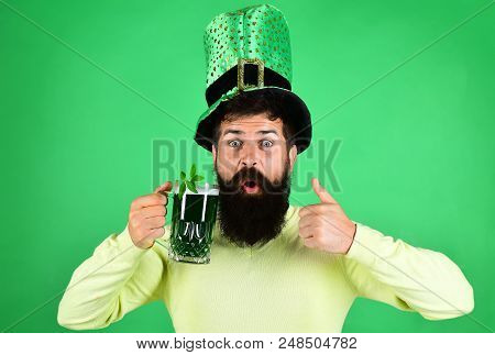 Saint Patrick's Day. Happy bearded man in yellow sweater holds glass of beer. Clover in glass of beer. Bearded leprechaun. Happy Irish leprechaun with black beard. Ireland tradition. Sign good. stock photo