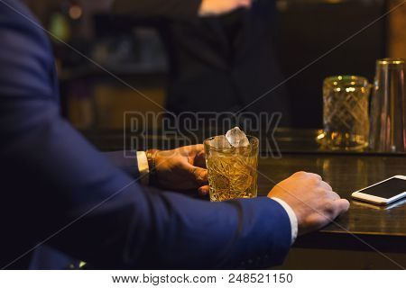 Businessman relieving stress after hard working day, drinking whiskey at bar, copy space stock photo
