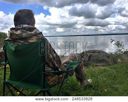 The man threw the fishing rods and waits for the fish to peck. Mixed media stock photo