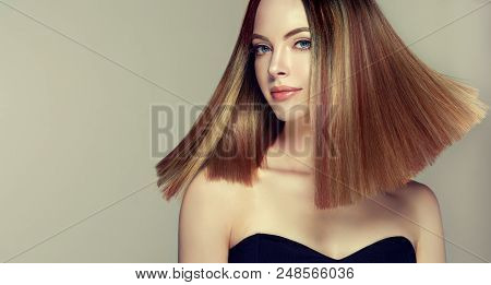 Beautiful model girl with shiny brown and straight long  hair . Keratin  straightening . Treatment, care and spa procedures. Medium length hairstyle. Coloring, ombre, shatush, balage and highlighting stock photo