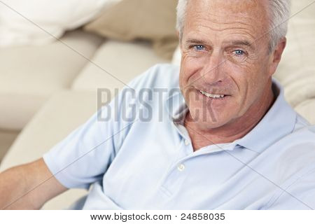 Happy and healthy senior man sitting on a sofa at home smiling and happy stock photo
