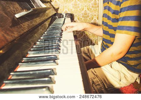 The boy studies chords on notes, sitting at the piano. stock photo