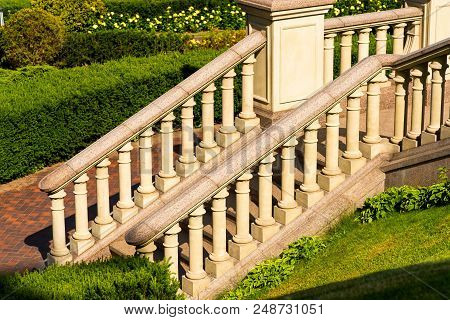 Stone steps with balusters and marble rails among the green landscape stock photo