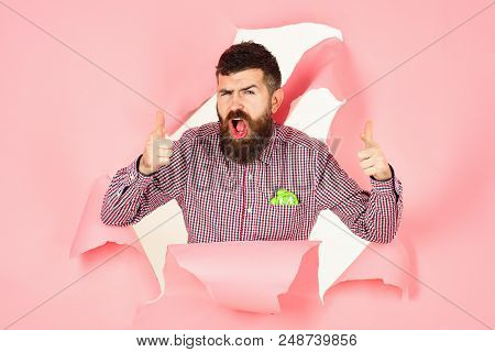 Saving time. Excited bearded man looking through hole in pink paper and holds clocks. Business concept. Saving time concept. Bearded man peeking through hole in pink paper. stock photo